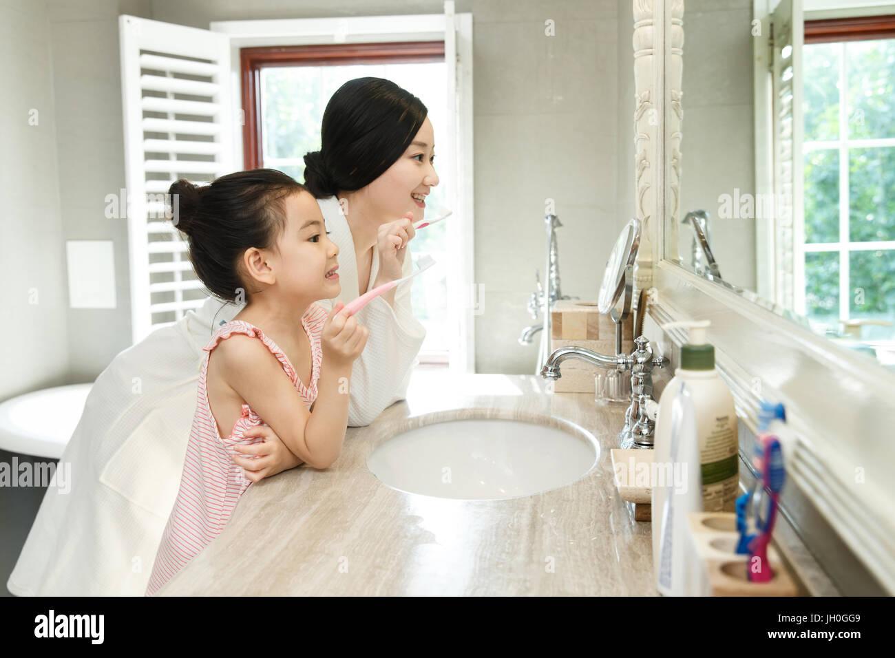 Mother teaching daughter brushing teeth - Stock Image