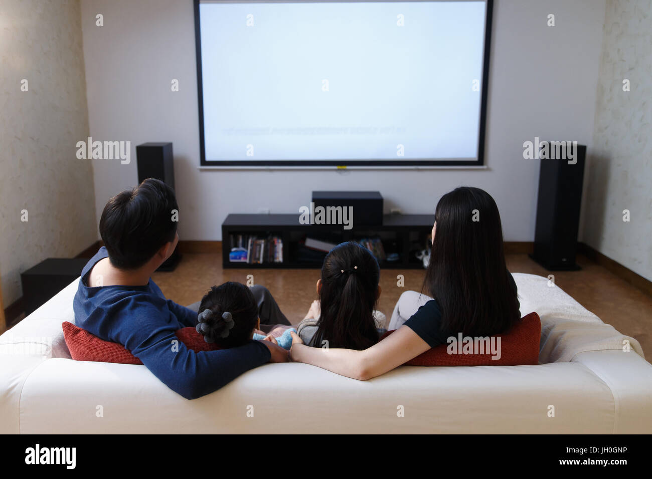 Happy family watching TV in sofa,back view - Stock Image