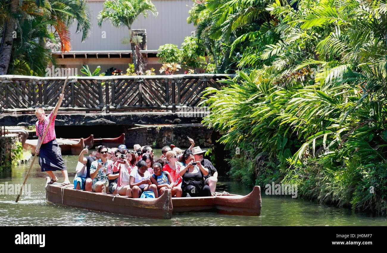 Honolulu, Hawaii - May 27, 2016:Visitors to the Polynesian Cultural Center, a popular tourist destination, are paddled Stock Photo
