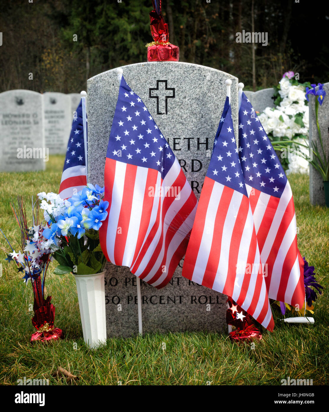 American flagz and  tombstones at an American National Cemetery. Stock Photo