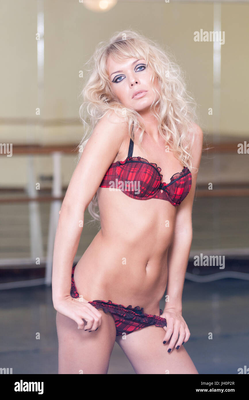 93719b7cd Beautiful woman with curly blond hair and blue eyes dressed in negligee  posing for beauty shots in a rehearsal studio