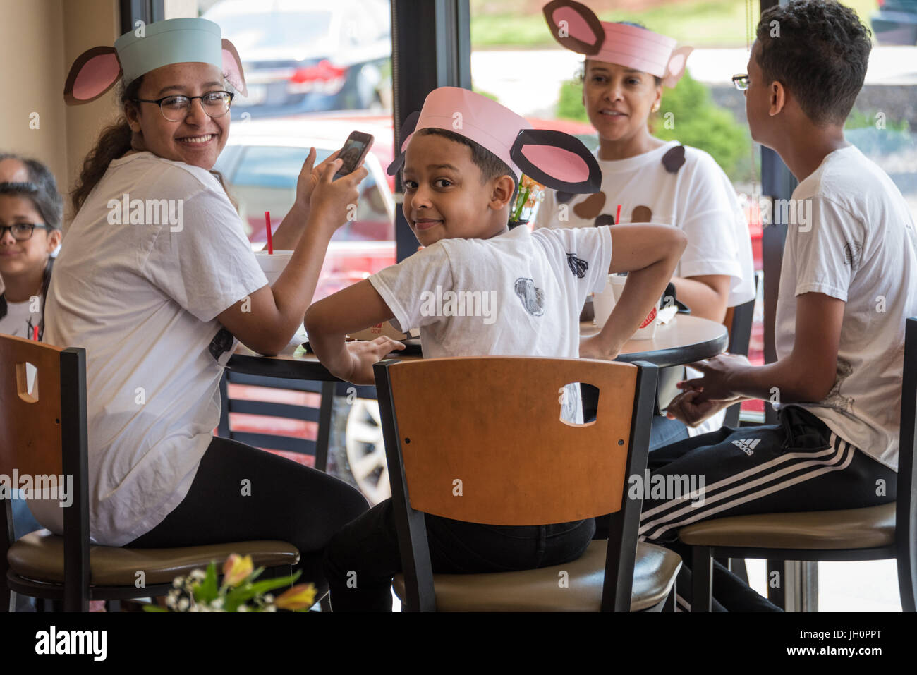 Chick-fil-A restaurant fans wearing homemade cow outfits for Chick-fil-A's Cow Appreciation Day. - Stock Image