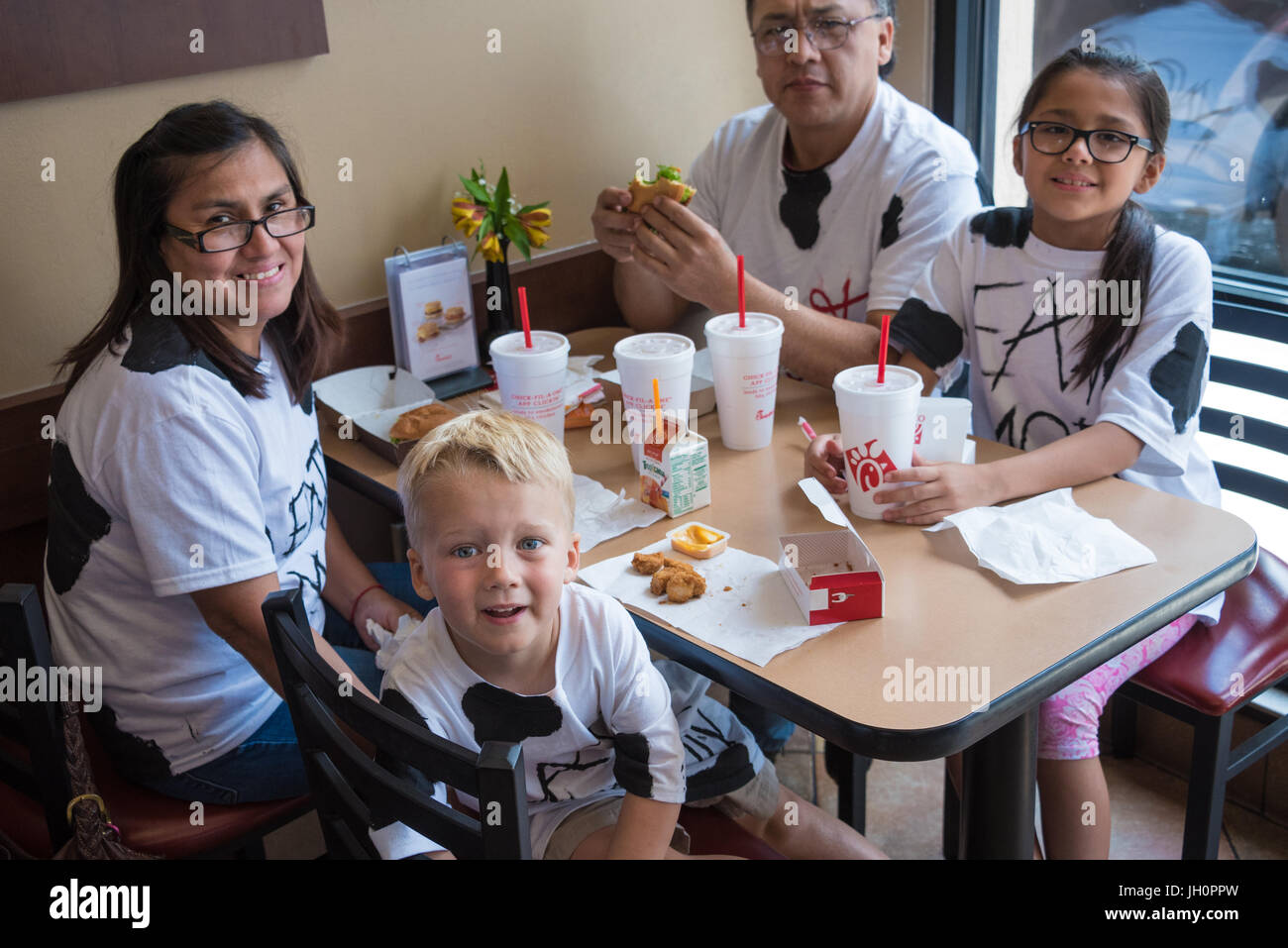 Chick-fil-A fans wearing homemade cow outfits for Chick-fil-A's Cow Appreciation Day. - Stock Image