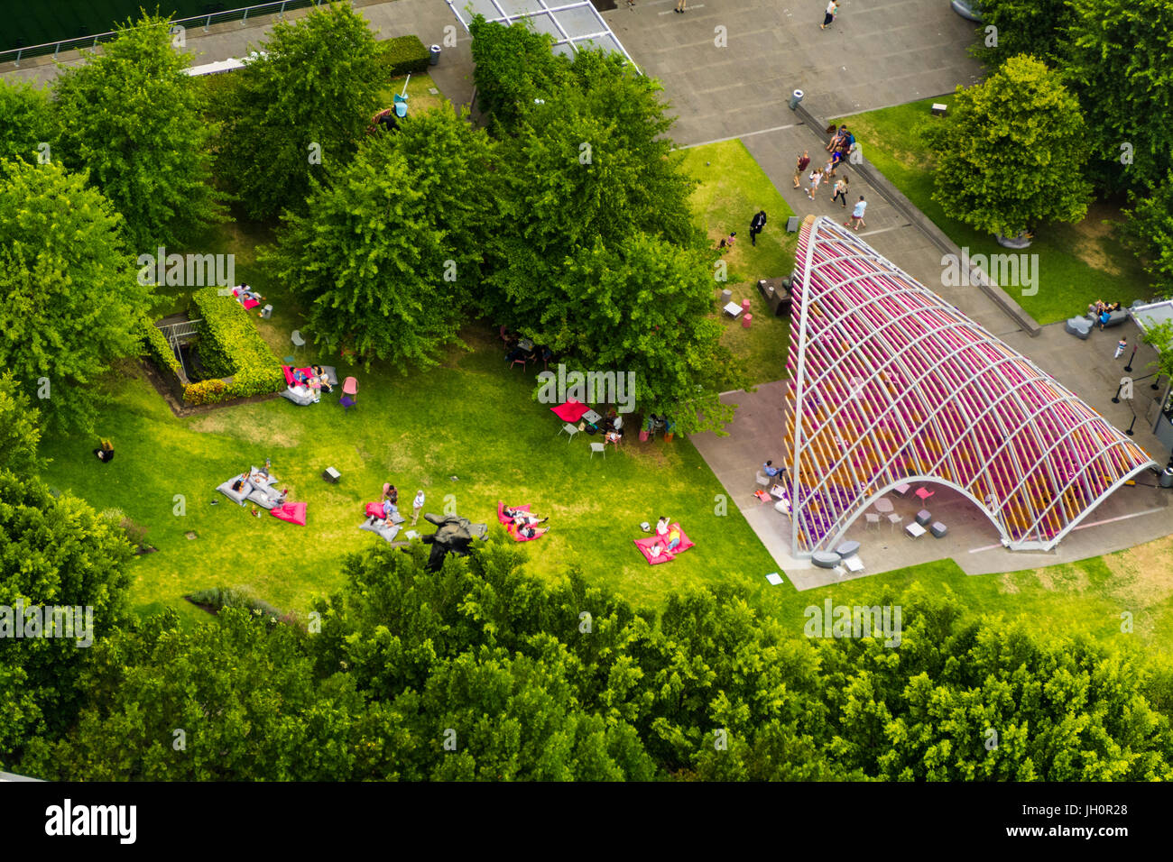people enjoying a garden park with bean bags and a colourful shelter - Stock Image