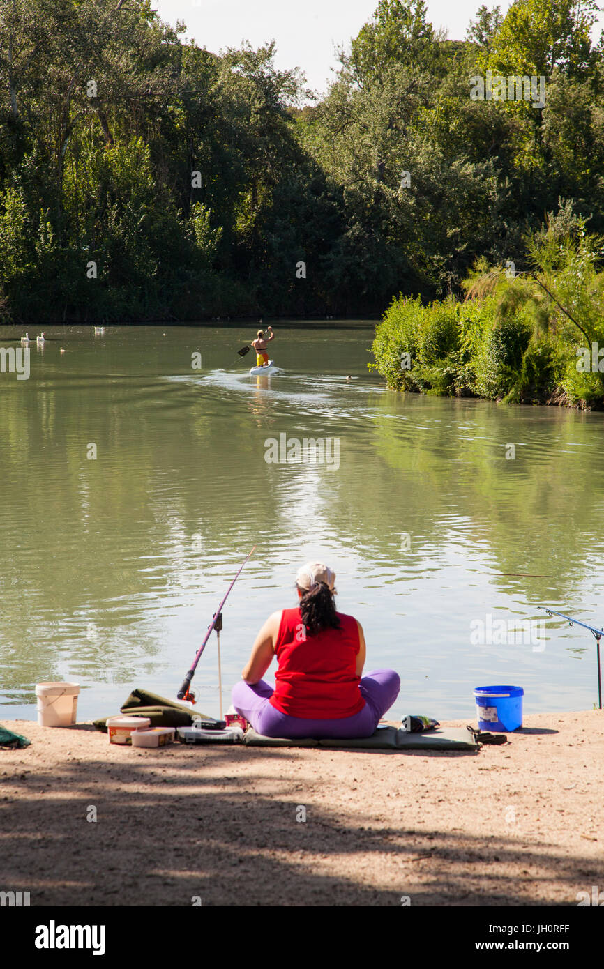 Woman fishing in the river Tagus at Aranjuez in the Madrid province of Spain  watching a paddle boarder go past - Stock Image