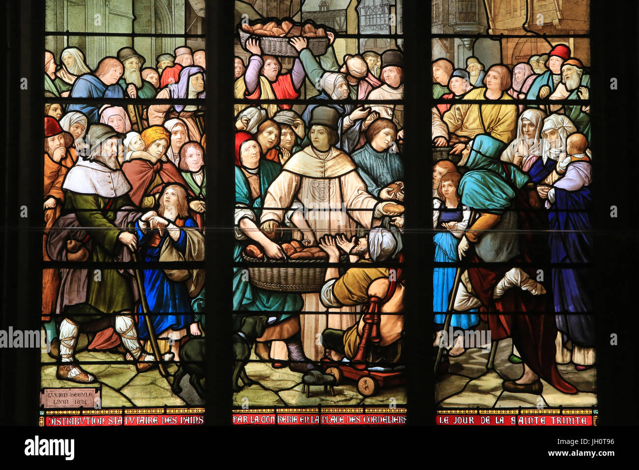 Trinity Brothers Helping the Poors. Stained glass. Saint-Nizier Church. Lyon. France. - Stock Image