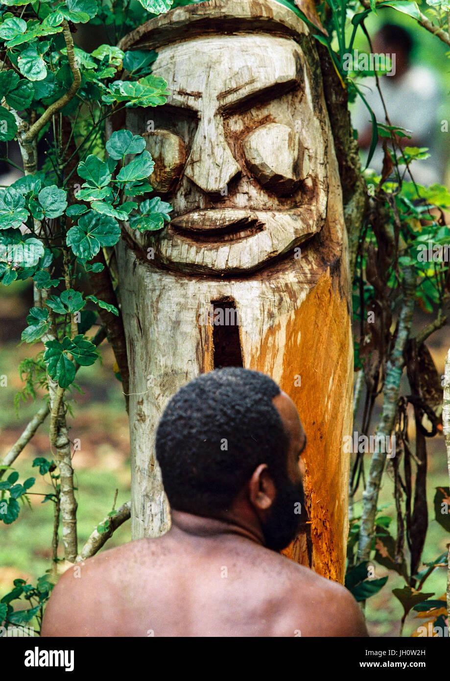 Tribesman beating a drum during a ceremony in the jungle, Malampa Province, Malekula Island, Vanuatu - Stock Image