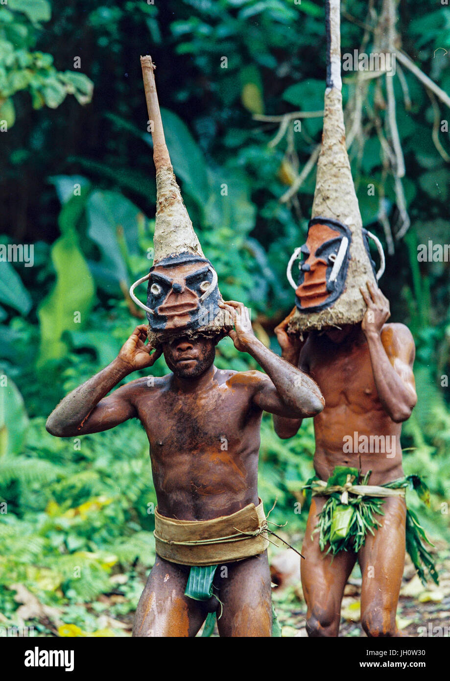 Tribesmen dancing in the jungle with helmet masks for a circumcision ceremony, Malampa Province, Malekula Island, - Stock Image