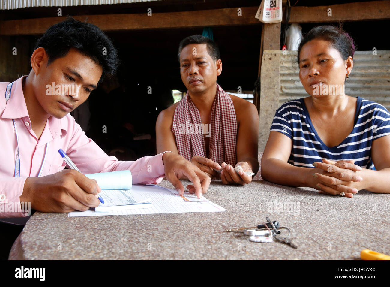 Chamroeun microfinance loan officer with clients Cambodia. - Stock Image