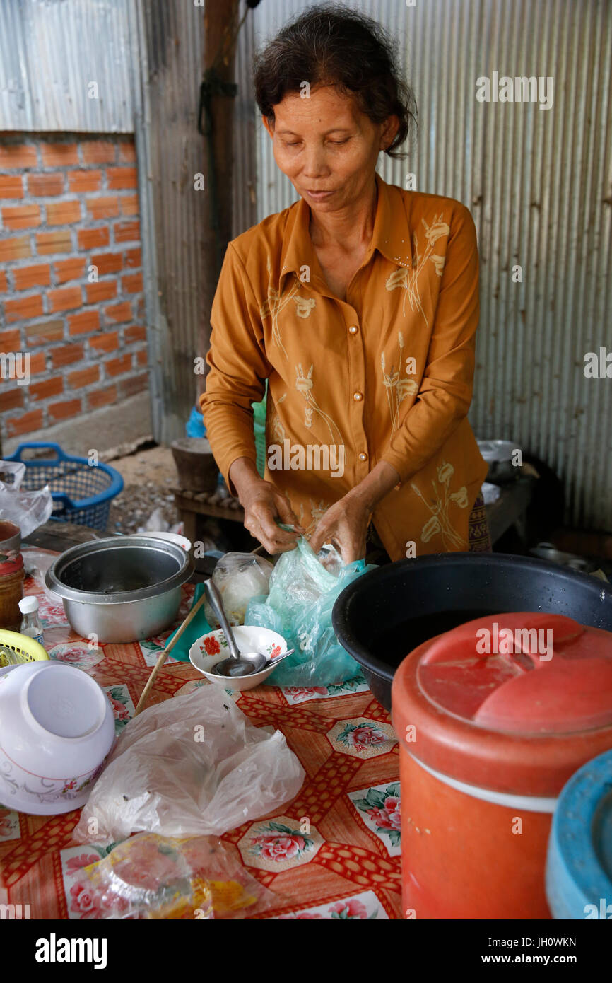 Chamroeun microfinance client Kean Ya in her grocery shop & catering business.   Cambodia. - Stock Image