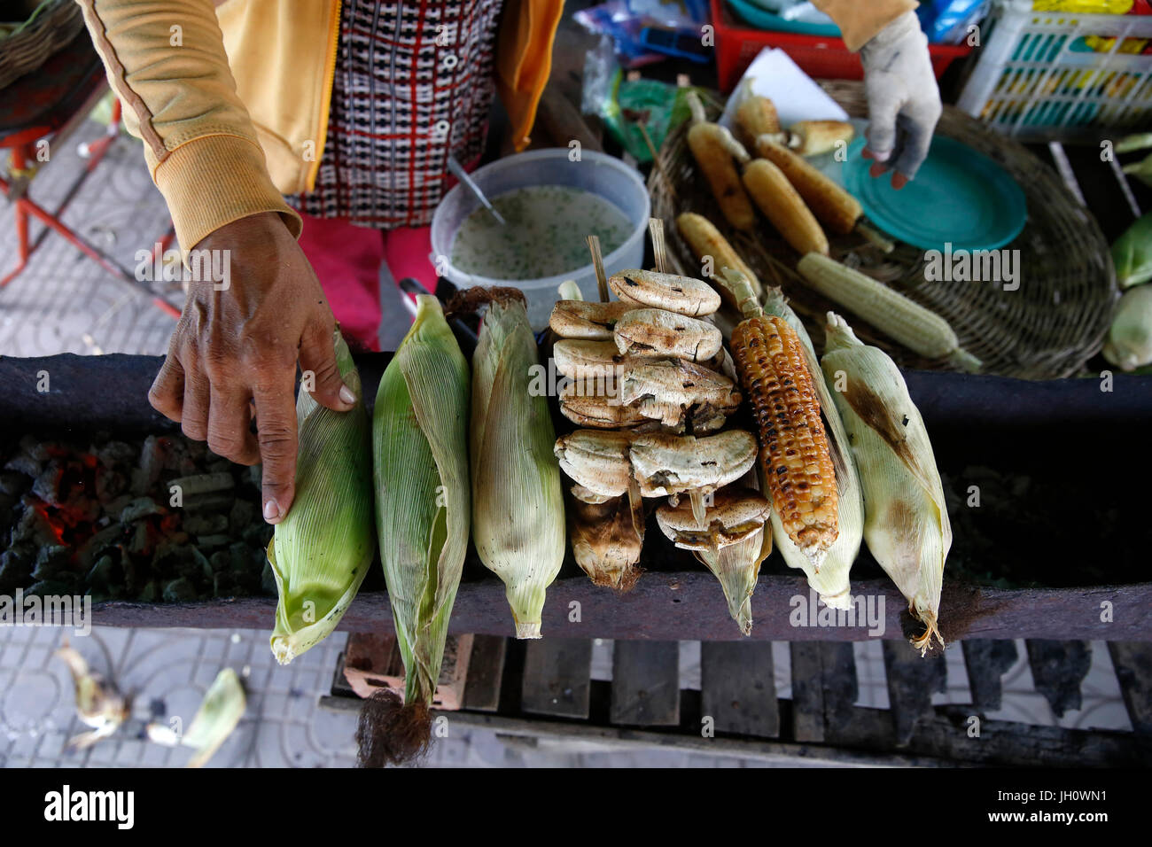 Tab Sreyneang runs a banana & corn roasting stand and a bicycle repair shop financed by a 1,4 million riel 1st - Stock Image
