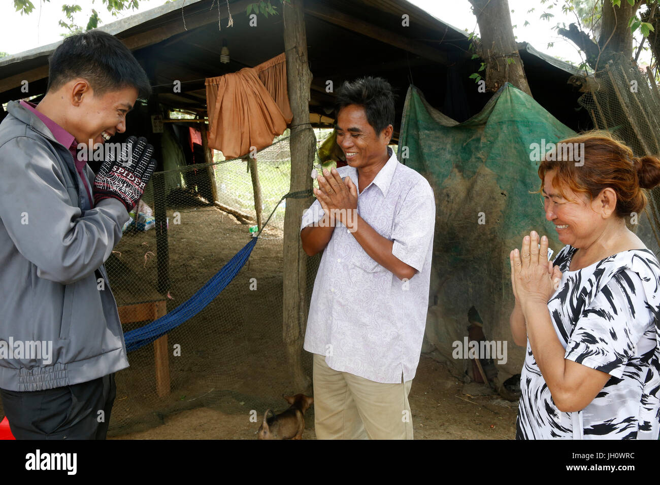 AMK microfinance employee greeting clients. Cambodia. - Stock Image