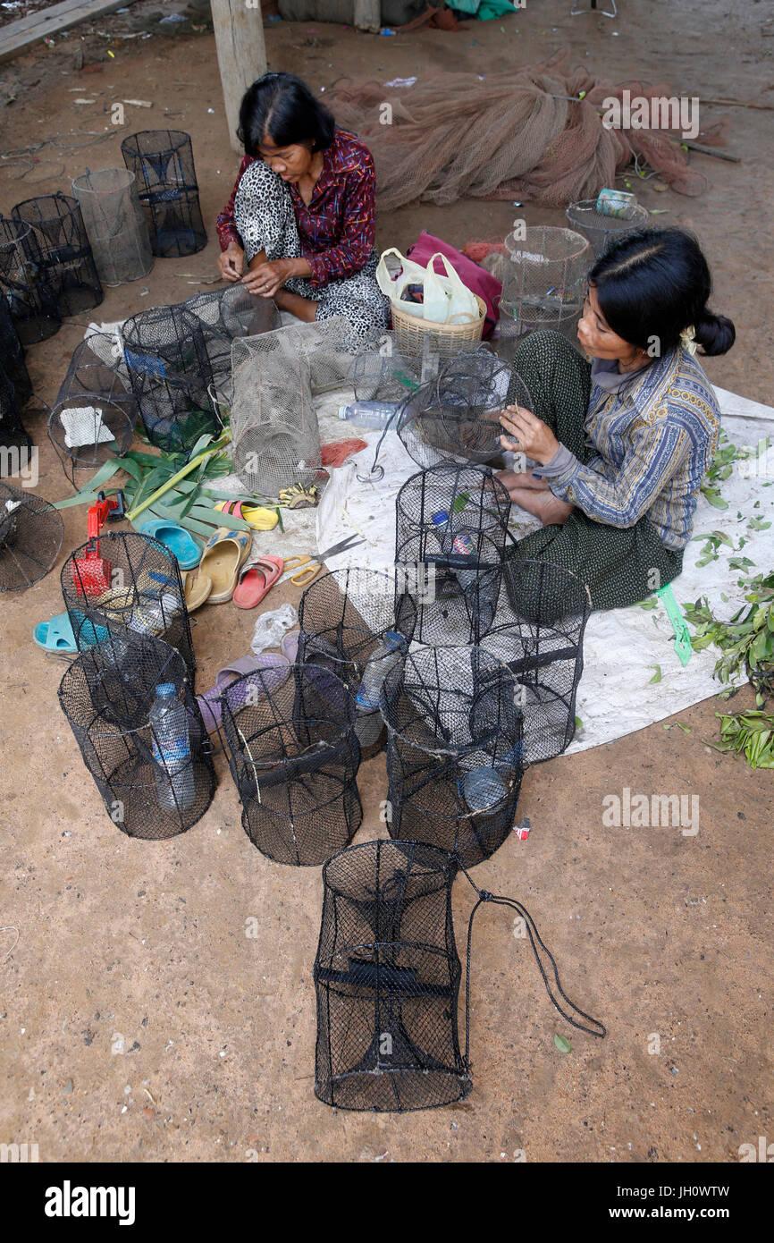 AMK microfinance clients repairing fishing equipment.   Cambodia. - Stock Image
