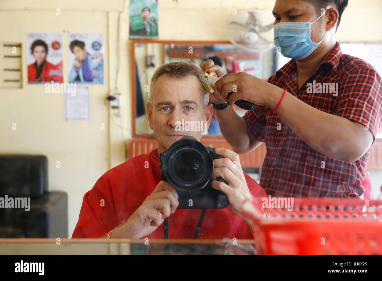 Photographer getting a haircut in Cambodia. Cambodia. - Stock Image