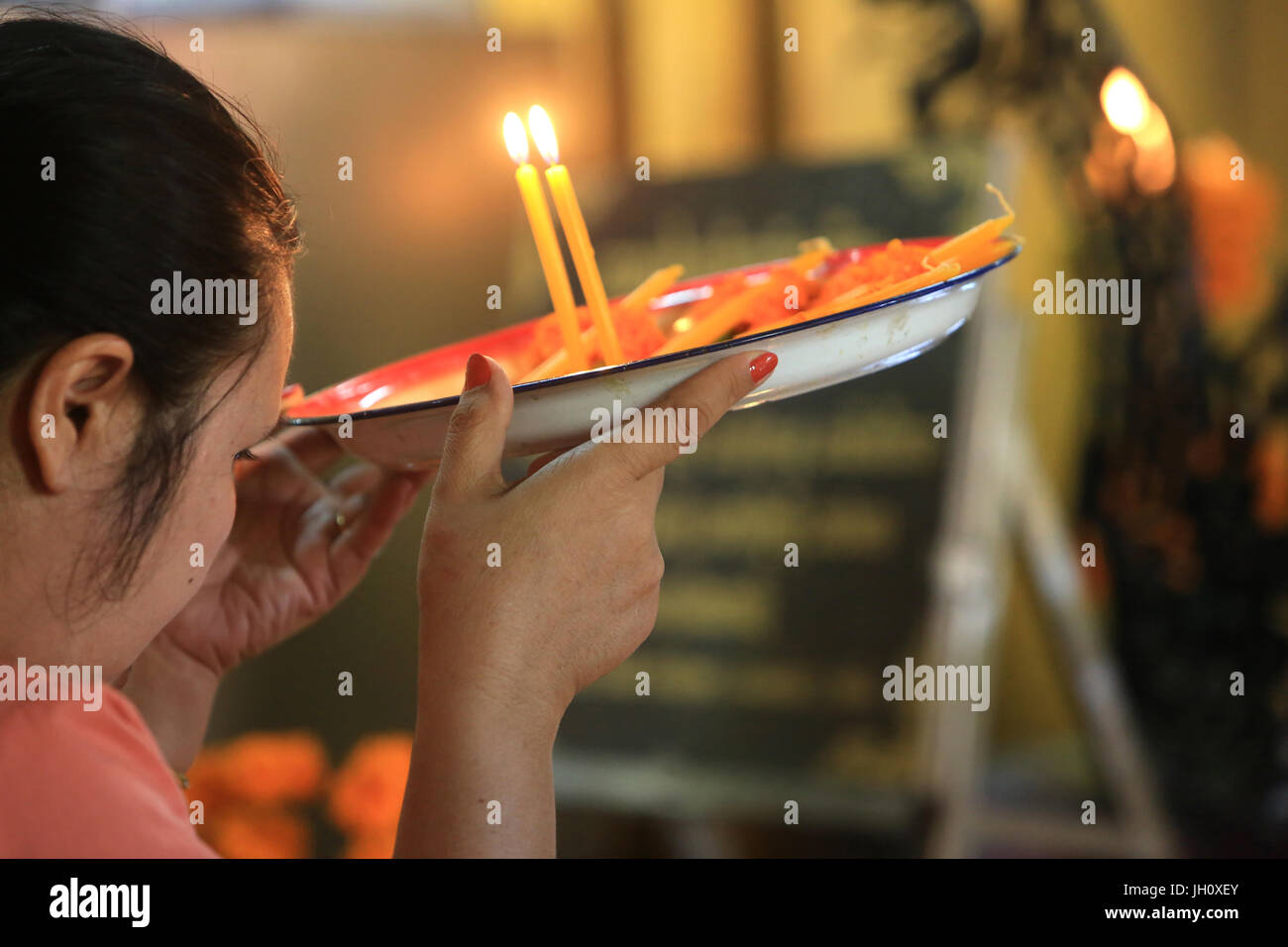 Worshiper praying with a tray of offerings. Buddhist ceremony. Wat Simuong. Wat Si Muang. Vientiane. Laos. - Stock Image
