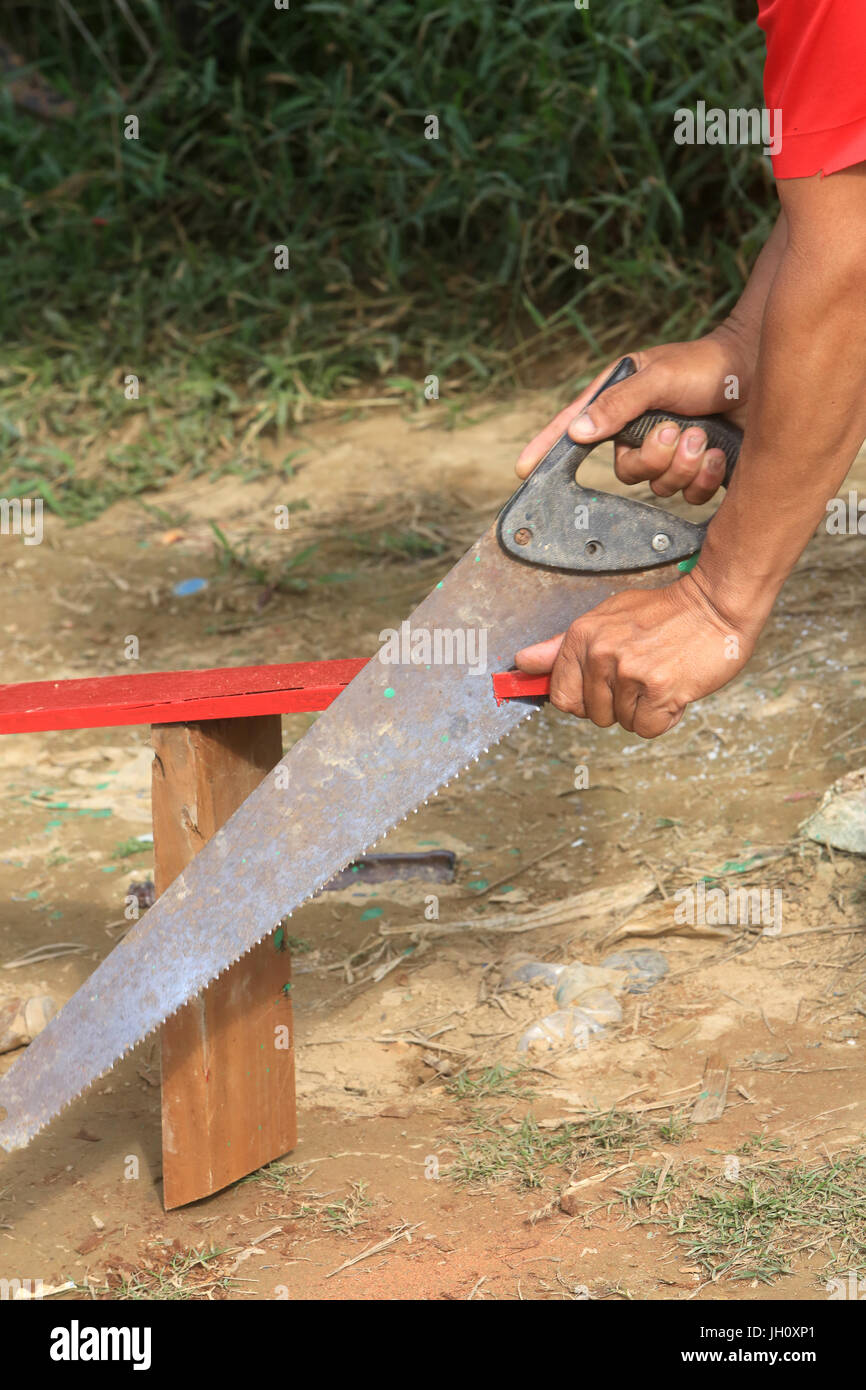 Lao sawing a wooden board for the renovation of his boat.  Laos. Stock Photo