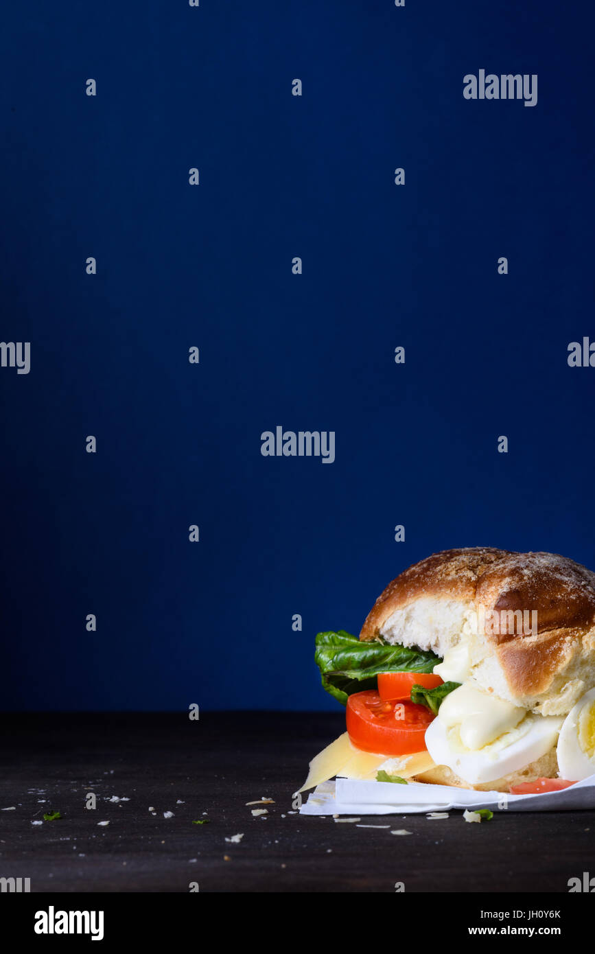 Veggie egg burger with cheese and tomatoes on a countertop, blue background, copy space. - Stock Image