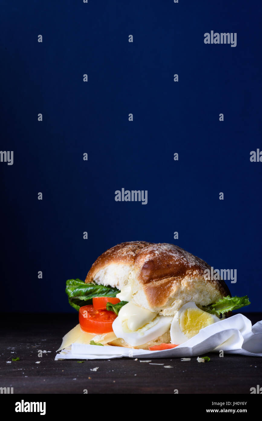 Delicious burger with egg, tomato, cheese, lettuce wooden counter. Copy space. - Stock Image