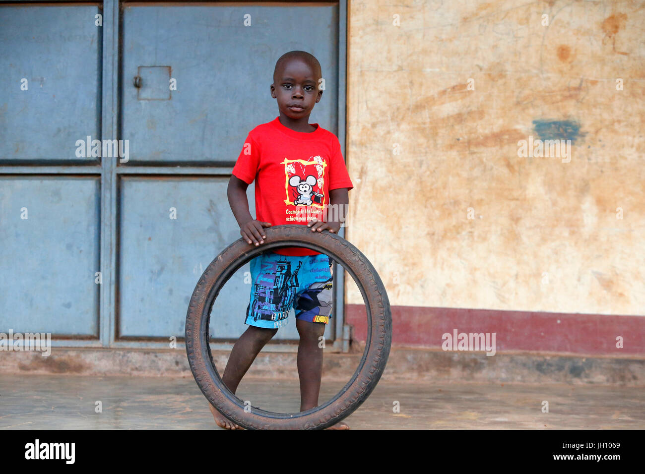 Ugandan child playing with a tyre. Uganda. - Stock Image