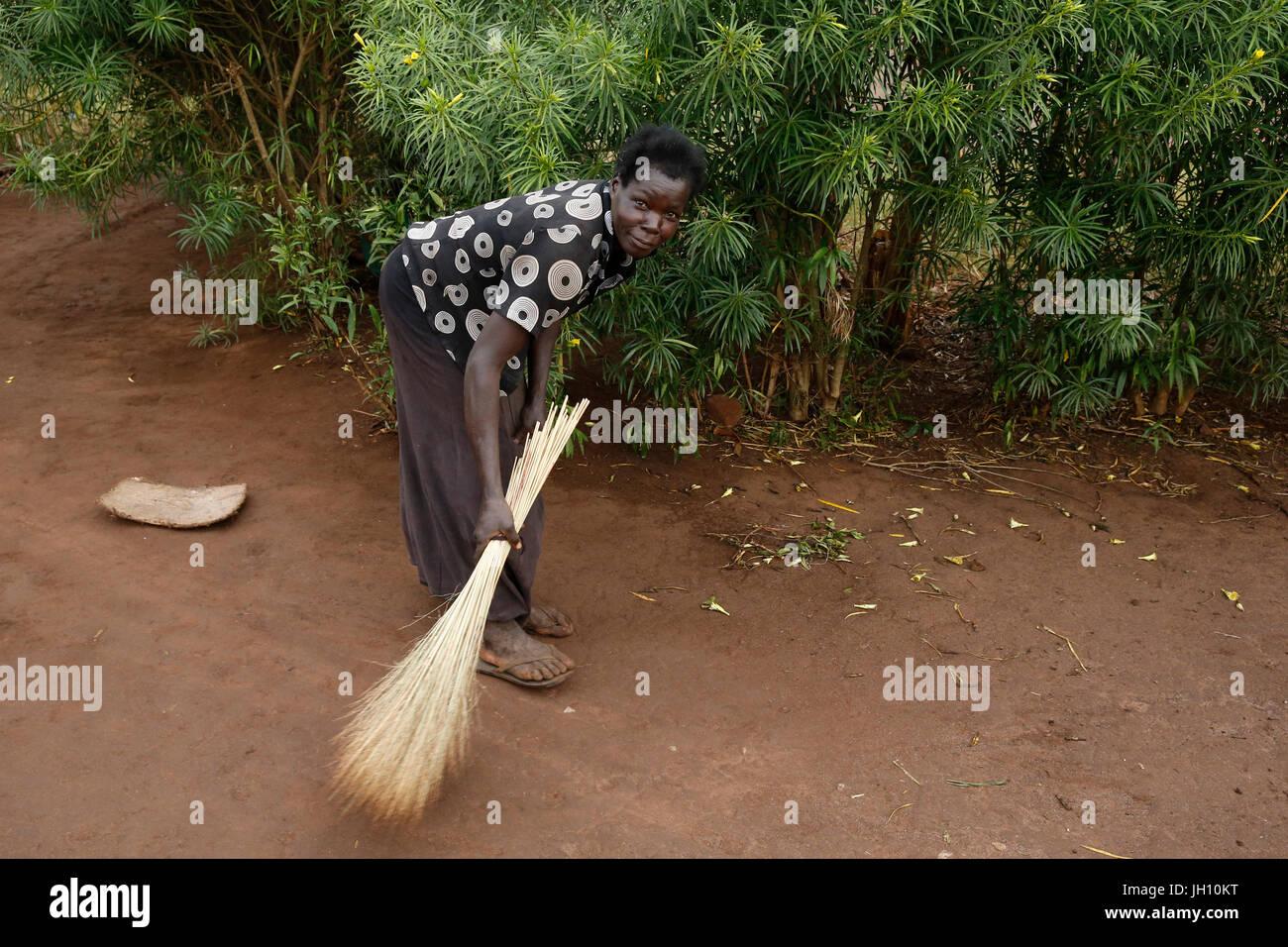 Woman sweeping the earth around her home. Uganda. - Stock Image
