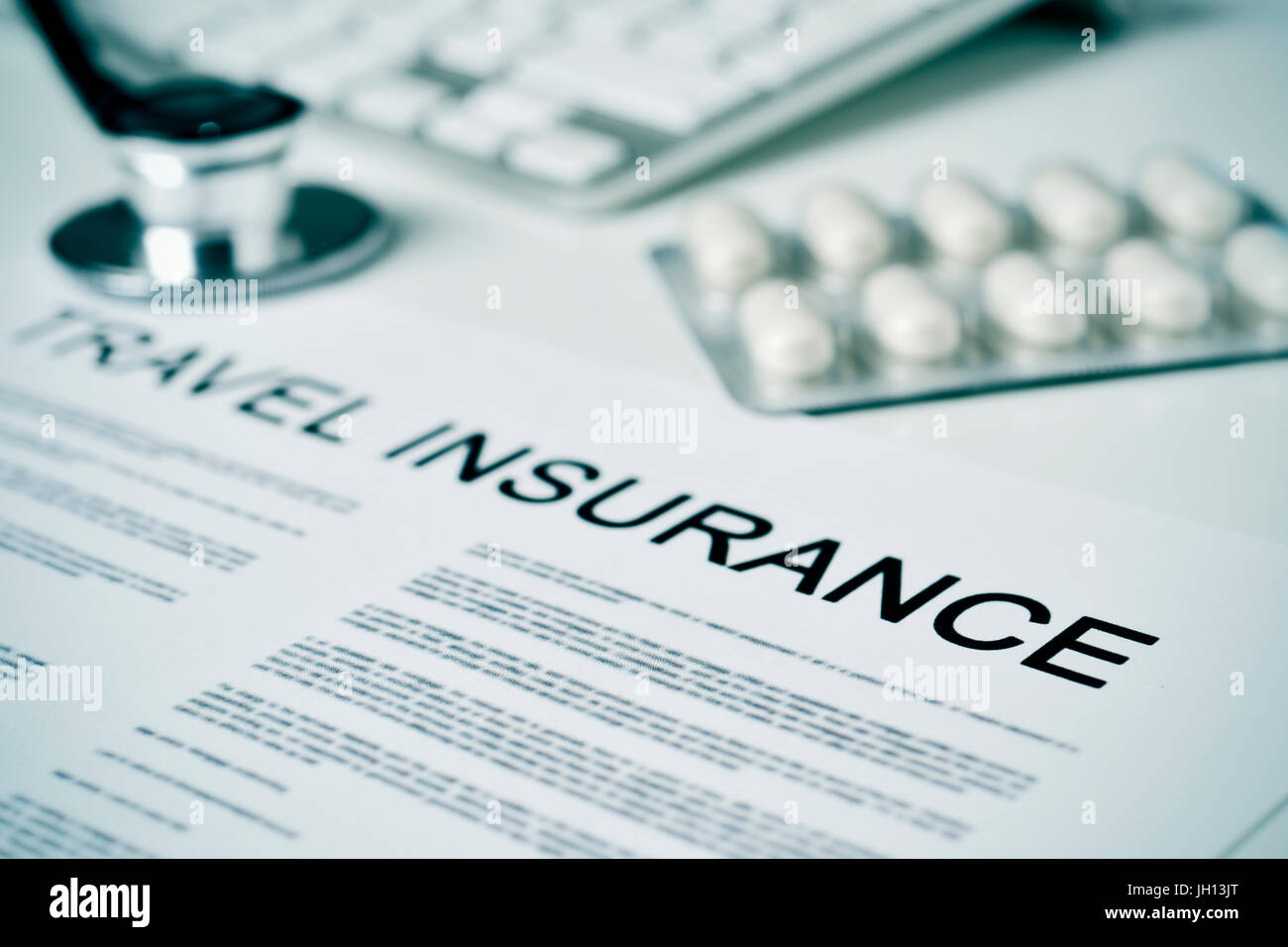 closeup of a travel insurance policy on a doctors office, next to a computer keyboard, a stethoscope and some pills - Stock Image
