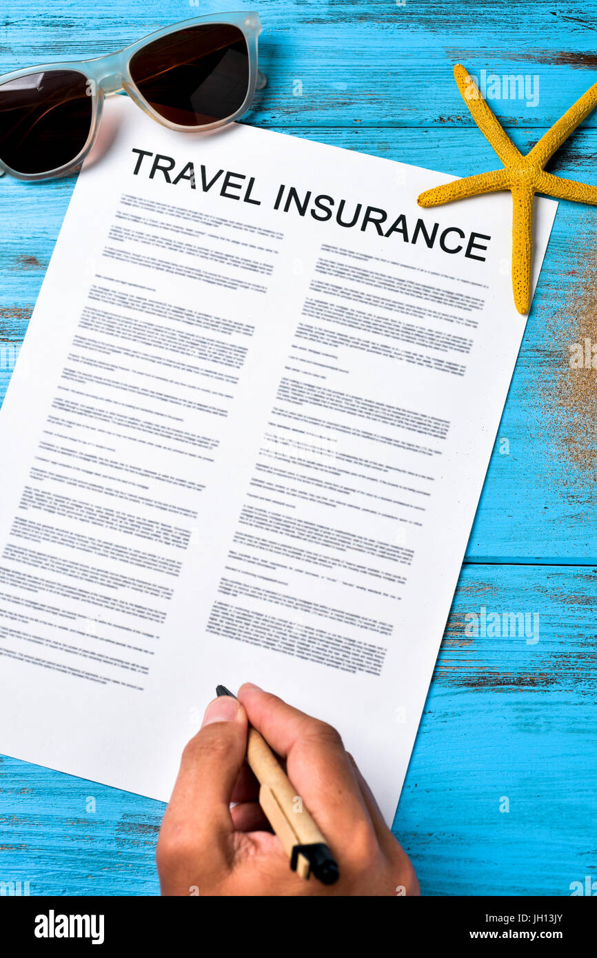 closeup of a young caucasian man signing a travel insurance contract on a colorful blue wooden table, next to a - Stock Image