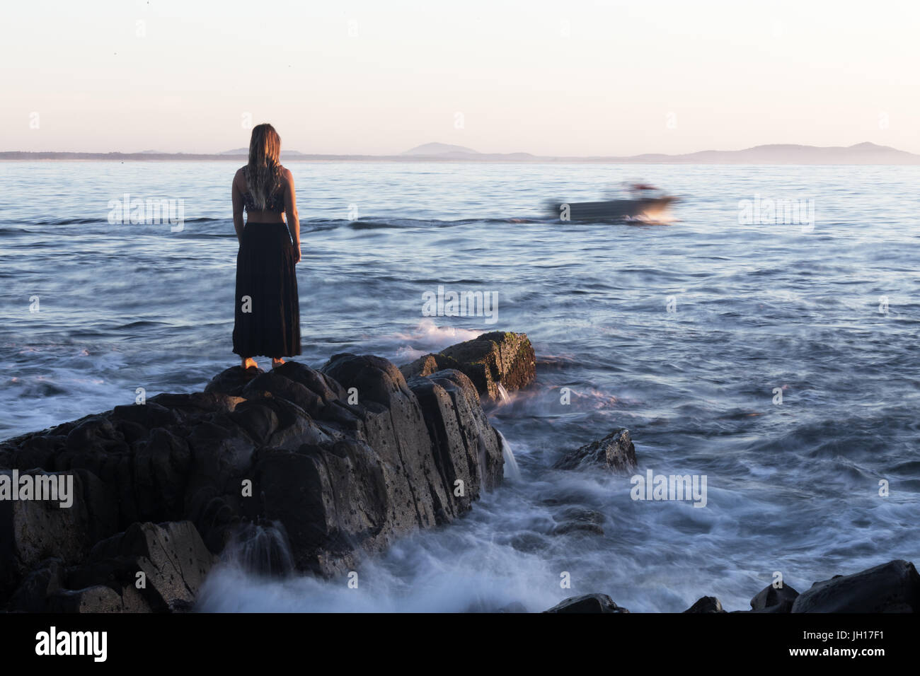 A woman watches from a rocky shoreline as a motion blurred boat goes by, heading out to sea. - Stock Image