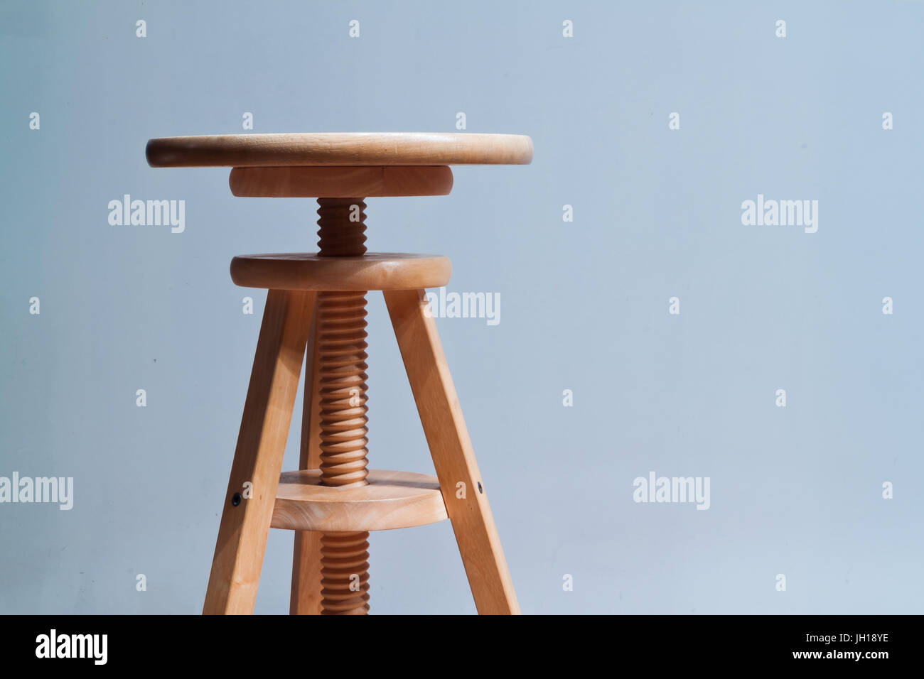 Three legged stool with adjustable seat - Stock Image