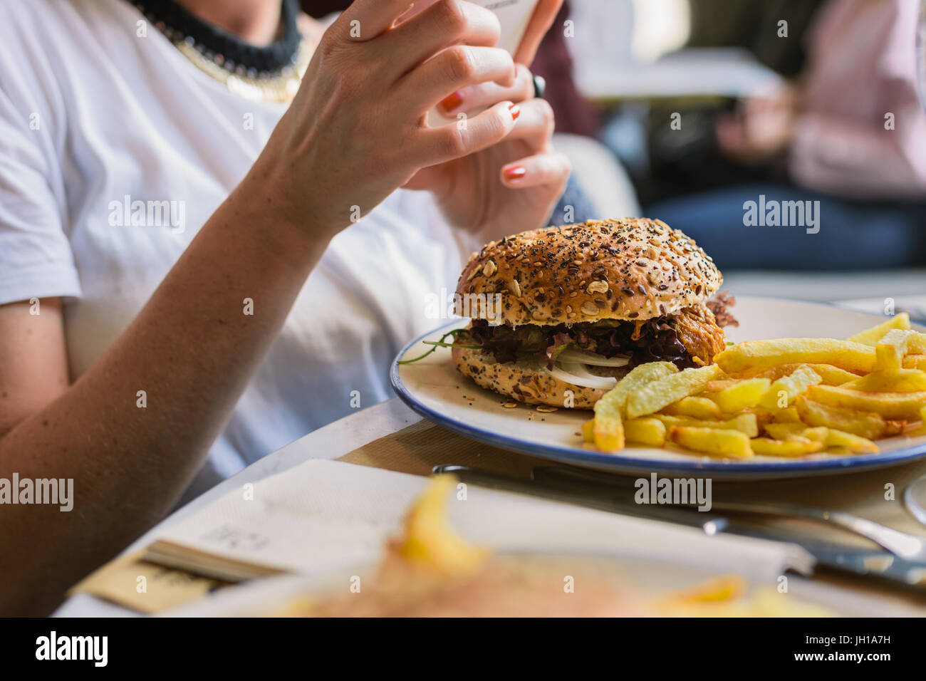 Beautiful woman eating burger and chips in restaurant while holding her mobile phone - Stock Image