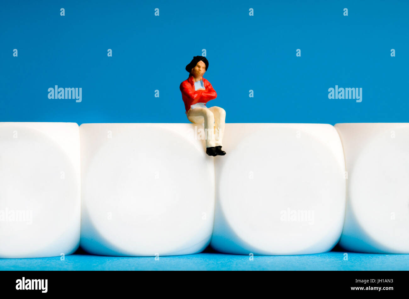 female miniature figurine sitting on white cubes, solitude, psychology and meditation concepts - Stock Image