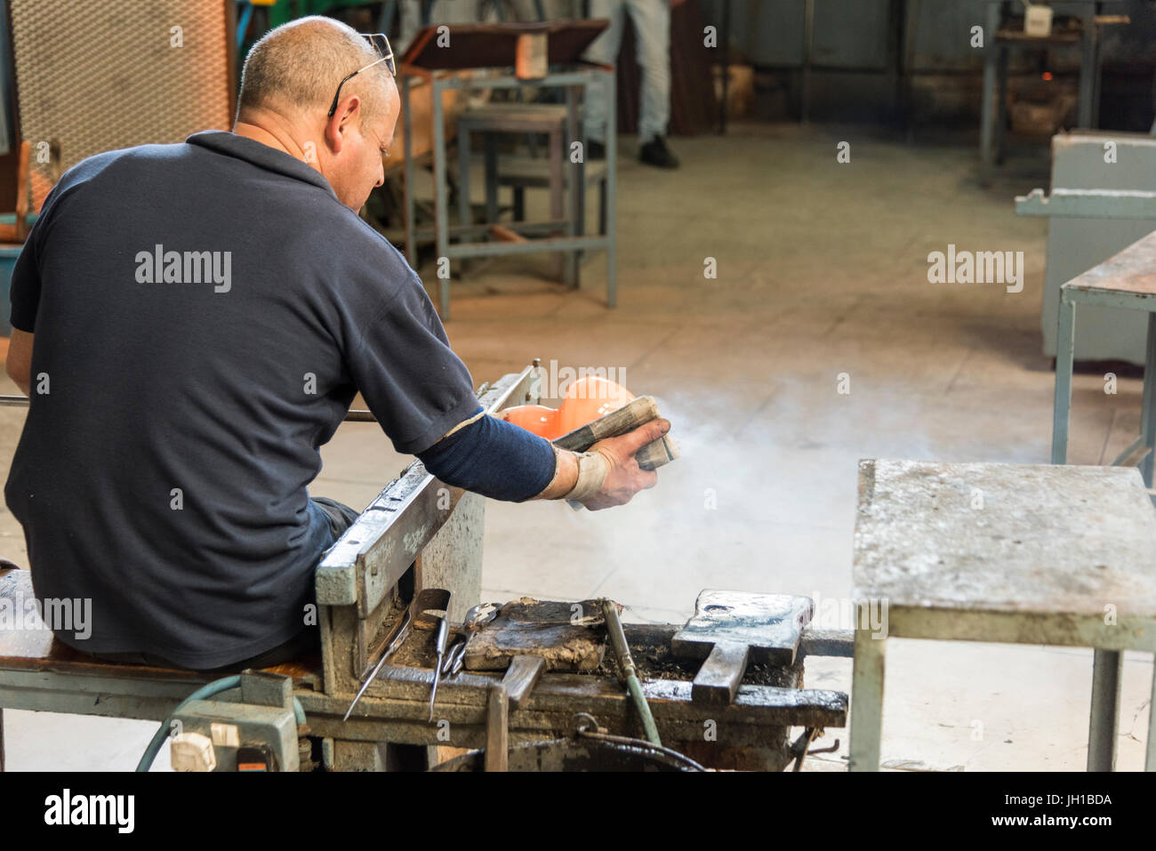 A glass blower at work making a glass bowl from molten glass in the Mdina Glass factory Malta - Stock Image