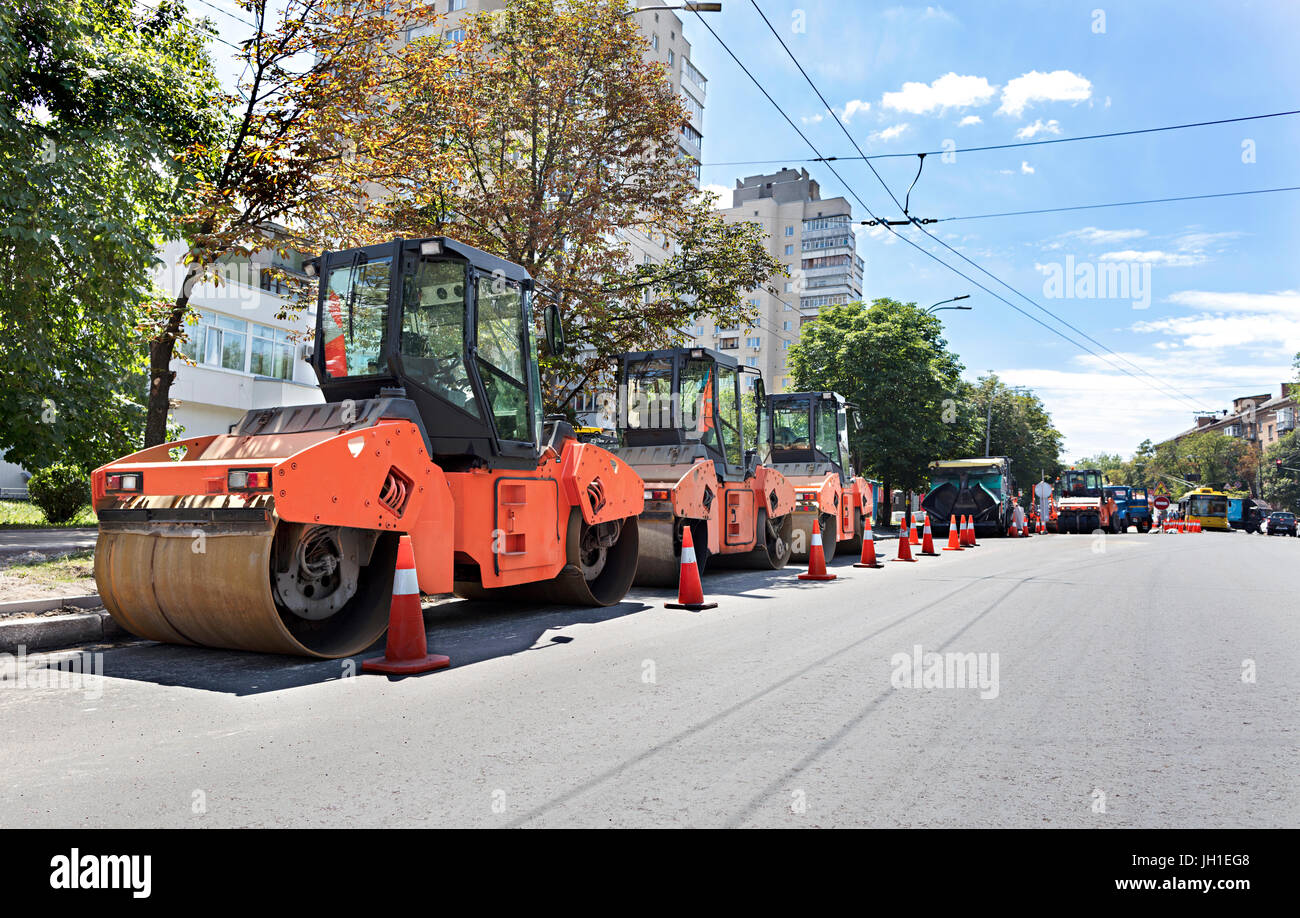 Among the summer noon three heavy road vibrating roller compactors and other equipment are ready for repair of the - Stock Image