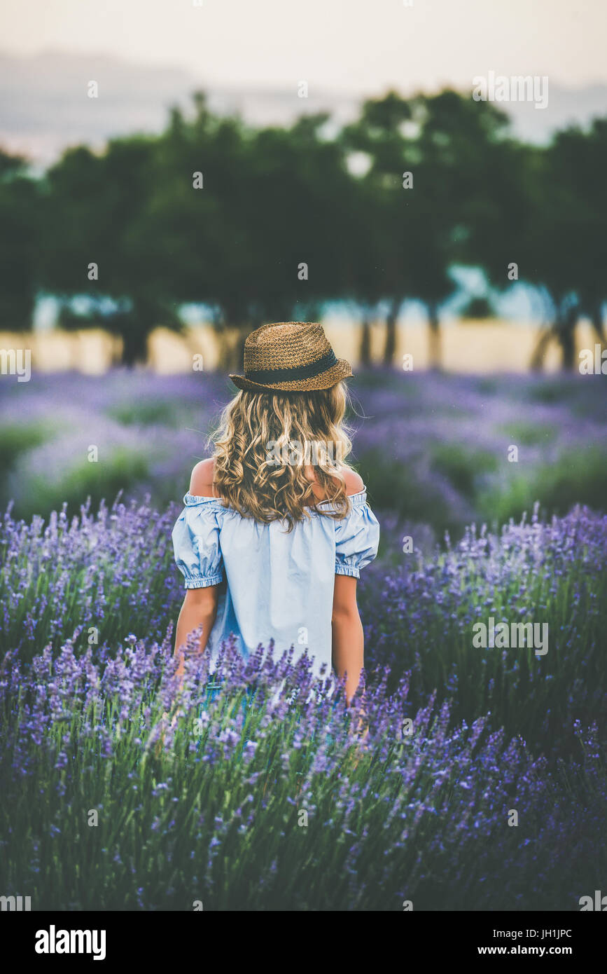 Young blond woman traveller standing in lavender field, Isparta, Turkey - Stock Image