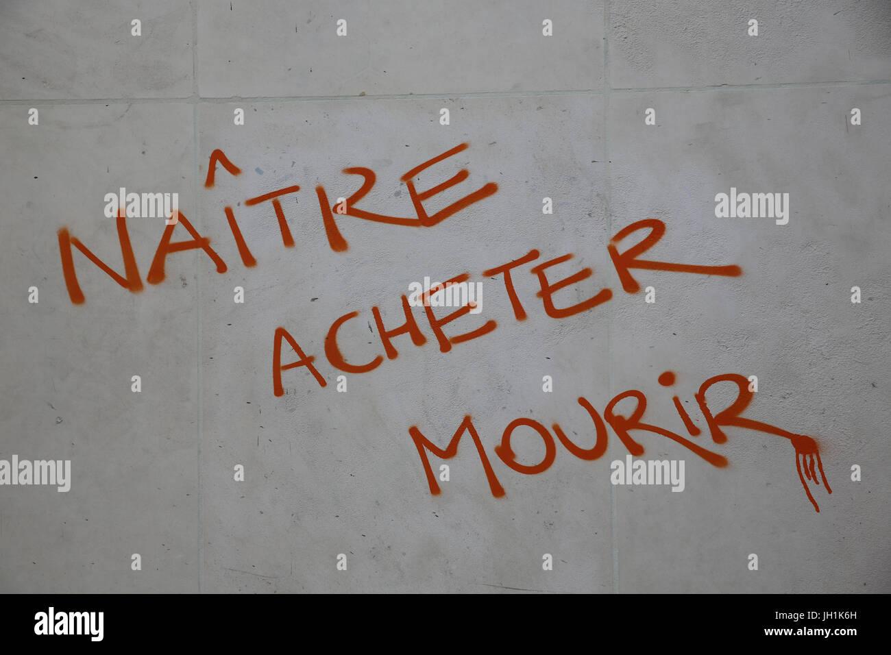 Anti-capitalist graffiti : being born, purchasing, dying. France. - Stock Image