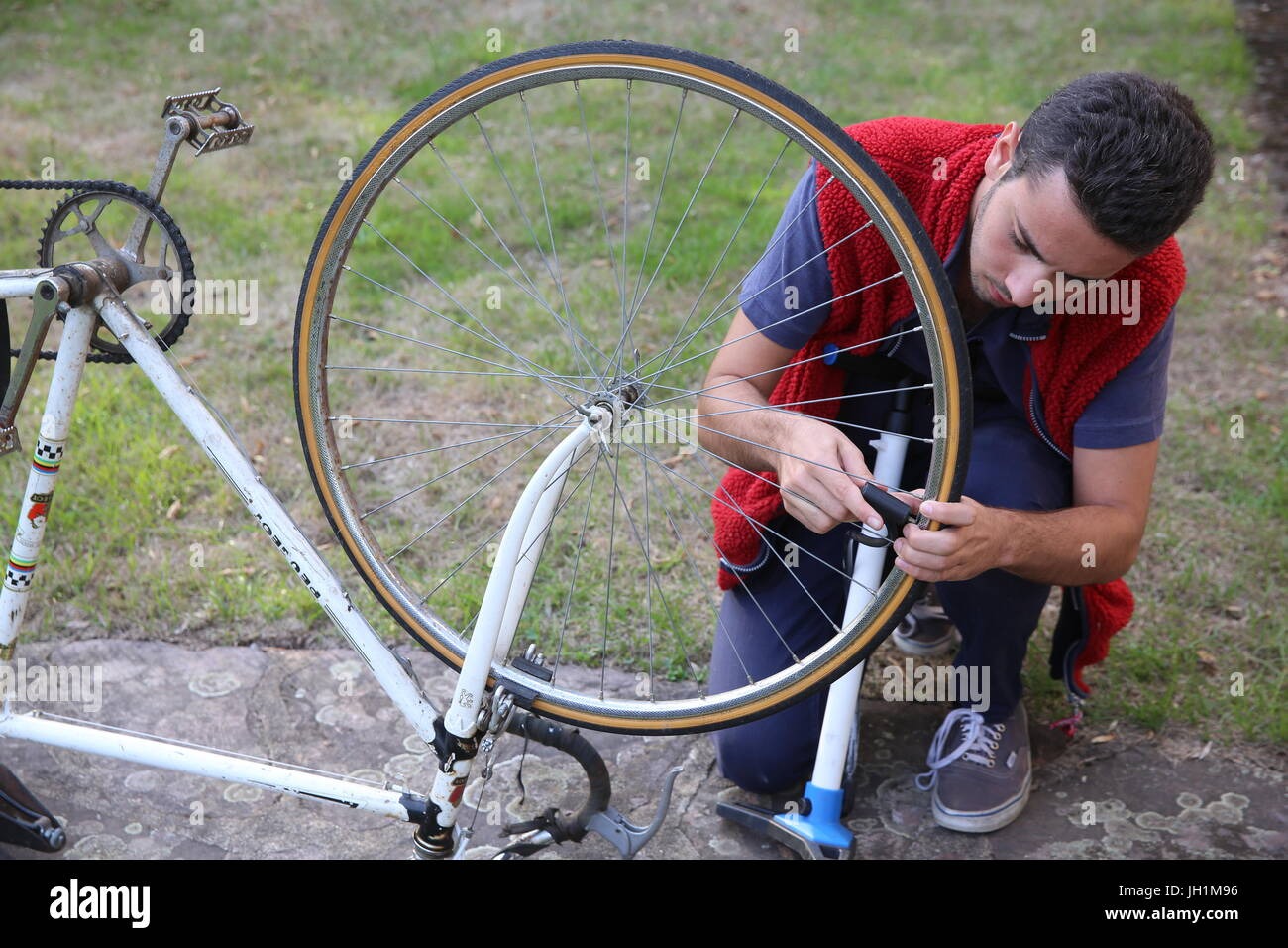 Young man inflating a bicycle tyre. France. - Stock Image