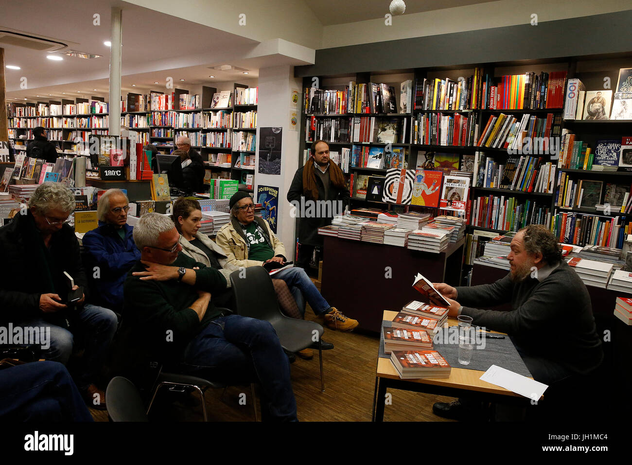French writer Mathias Enard reading one of his books in a bookshop. France. - Stock Image