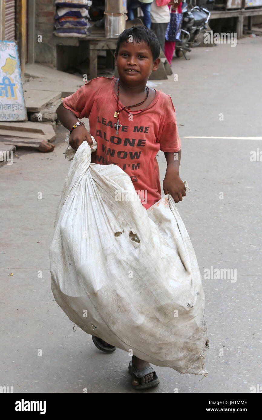 Boy carrying a bag of rubbish. India. - Stock Image