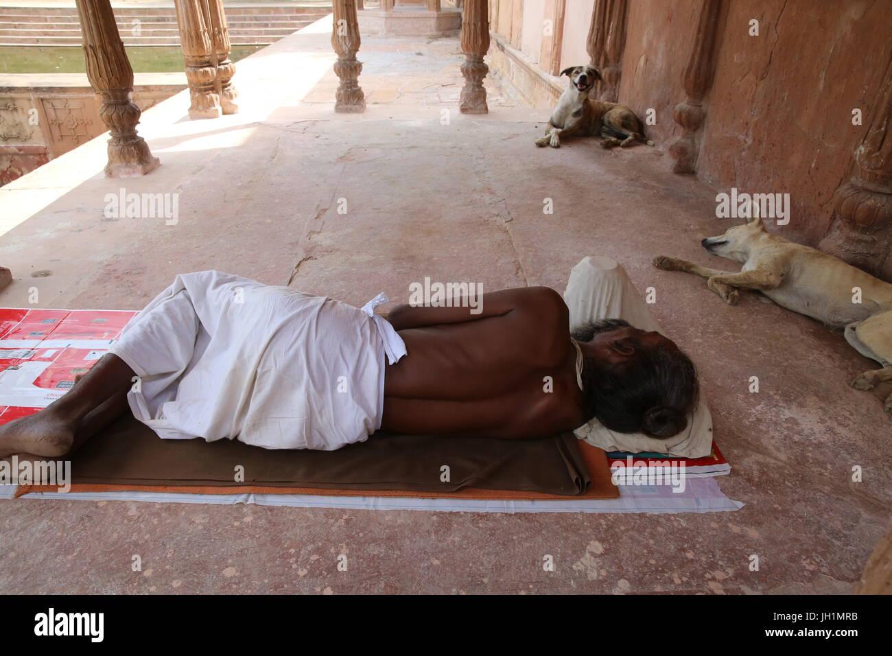 Sadhu sleeping in Kusum Sarovar. India. - Stock Image