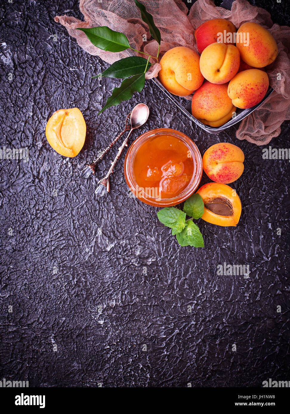 Apricot jam in glass jar. Selective focus - Stock Image
