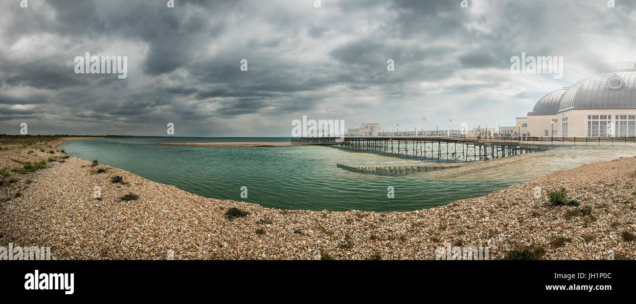 Seaside pier superimposed on a primitive landscape to illustrate 'return to nature' and climate change issues. - Stock Image