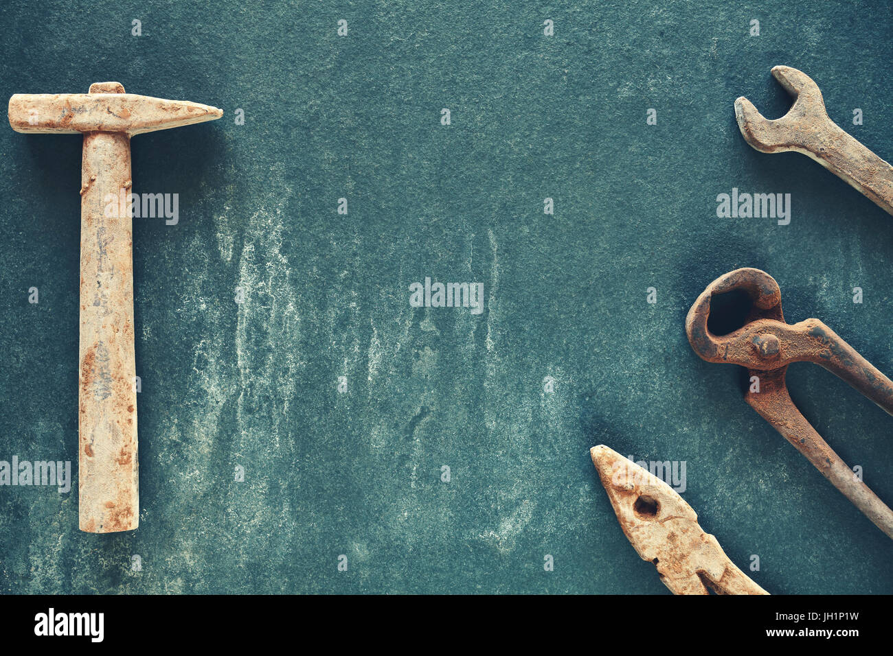 Retro stylized rusty like tools made of chocolate on a dark slate background, copy space in the middle. - Stock Image