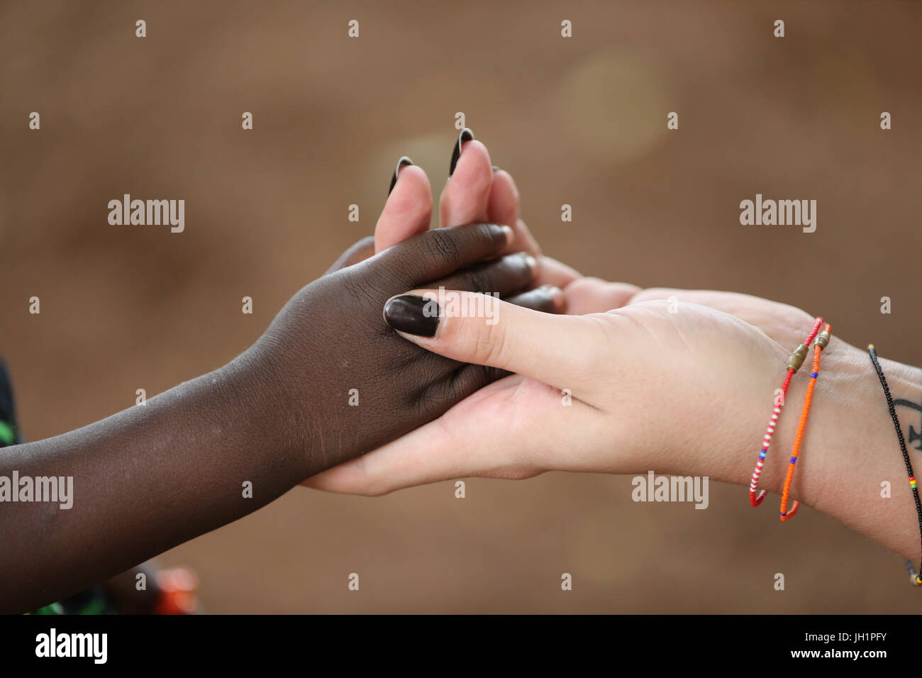 Humanitarian Worker Holding Child's Hand. Togo. - Stock Image