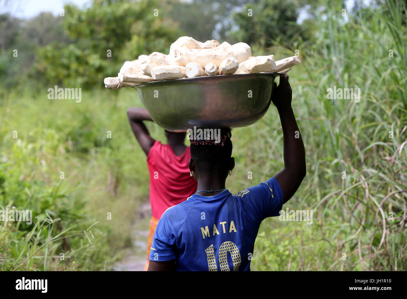 Women carrying platter with cassava on head. Togo. Stock Photo
