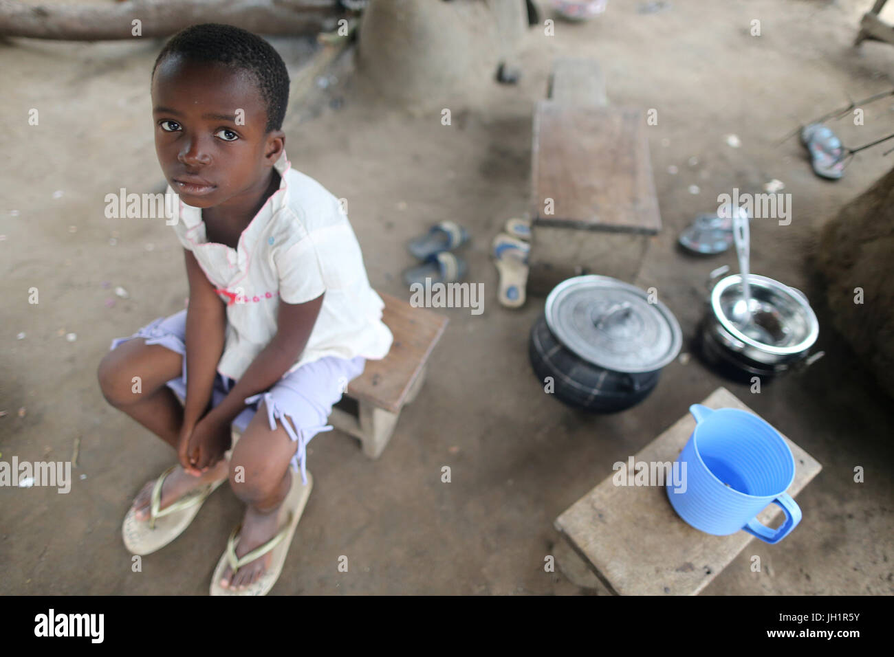African village. Girl siiting on a stool.  Togo. - Stock Image