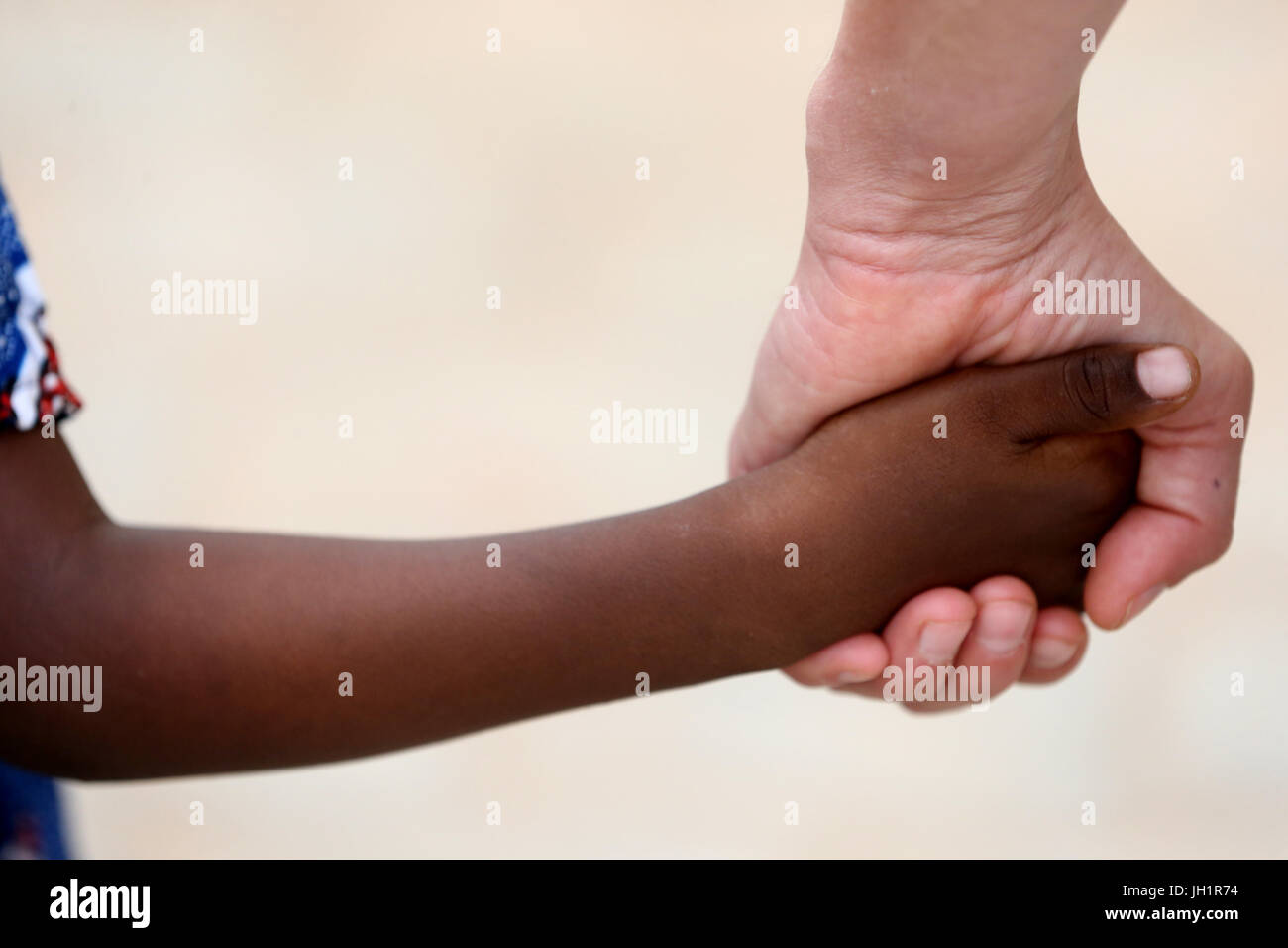 Humanitarian Worker Holding Child's Hand. Lome. Togo. - Stock Image