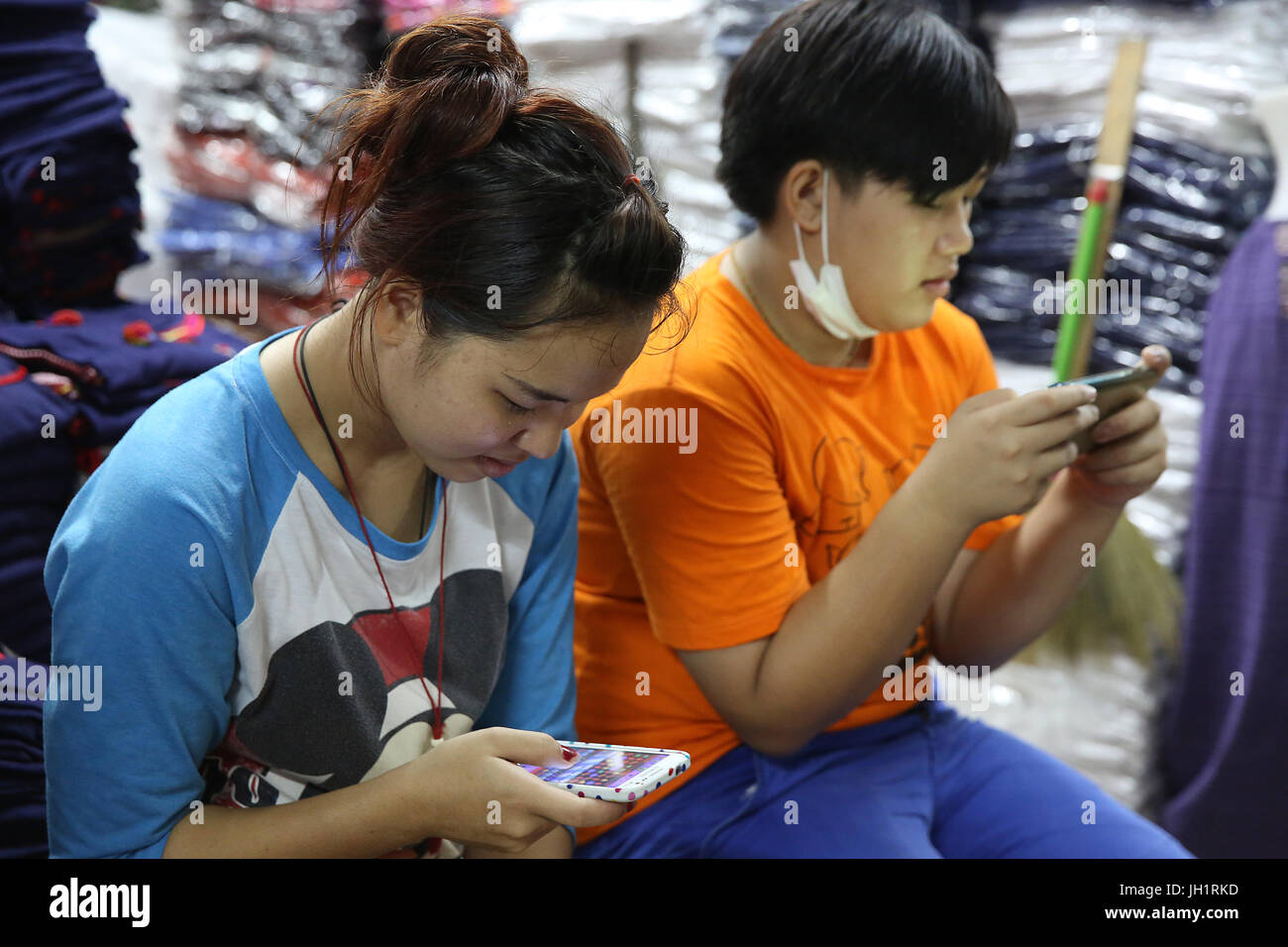 Thai shopkeepers using cell phones. Thailand. - Stock Image