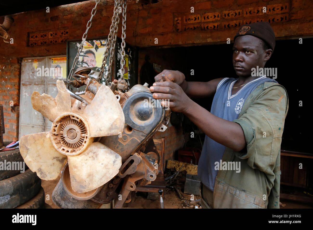 Apprentice working in a garage financed with a loan from ENCOT microfinance. Uganda. - Stock Image