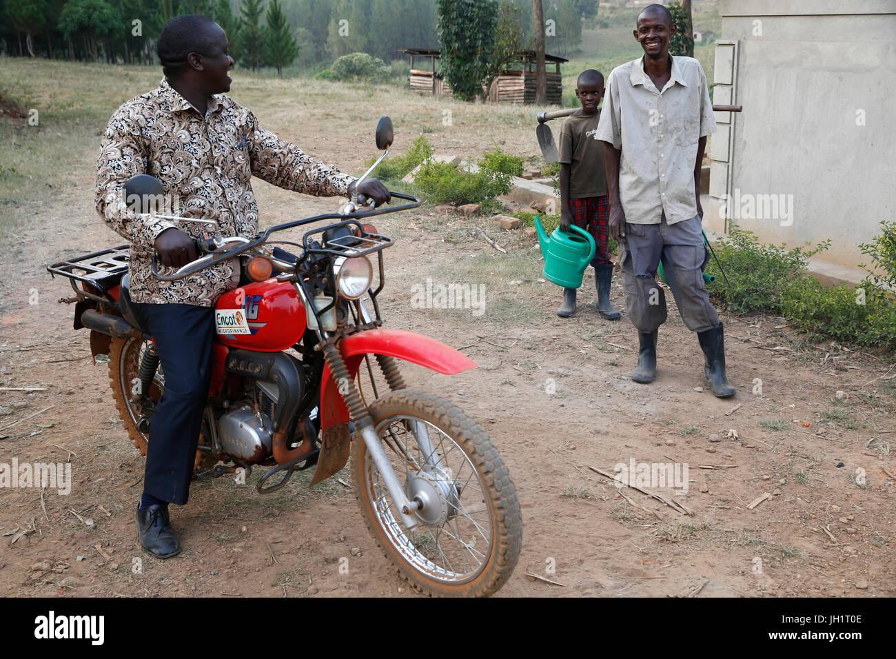 ENCOT microfinance branch manager Francis Buguma visiting farmer client Apollo Byarunga. Uganda. - Stock Image