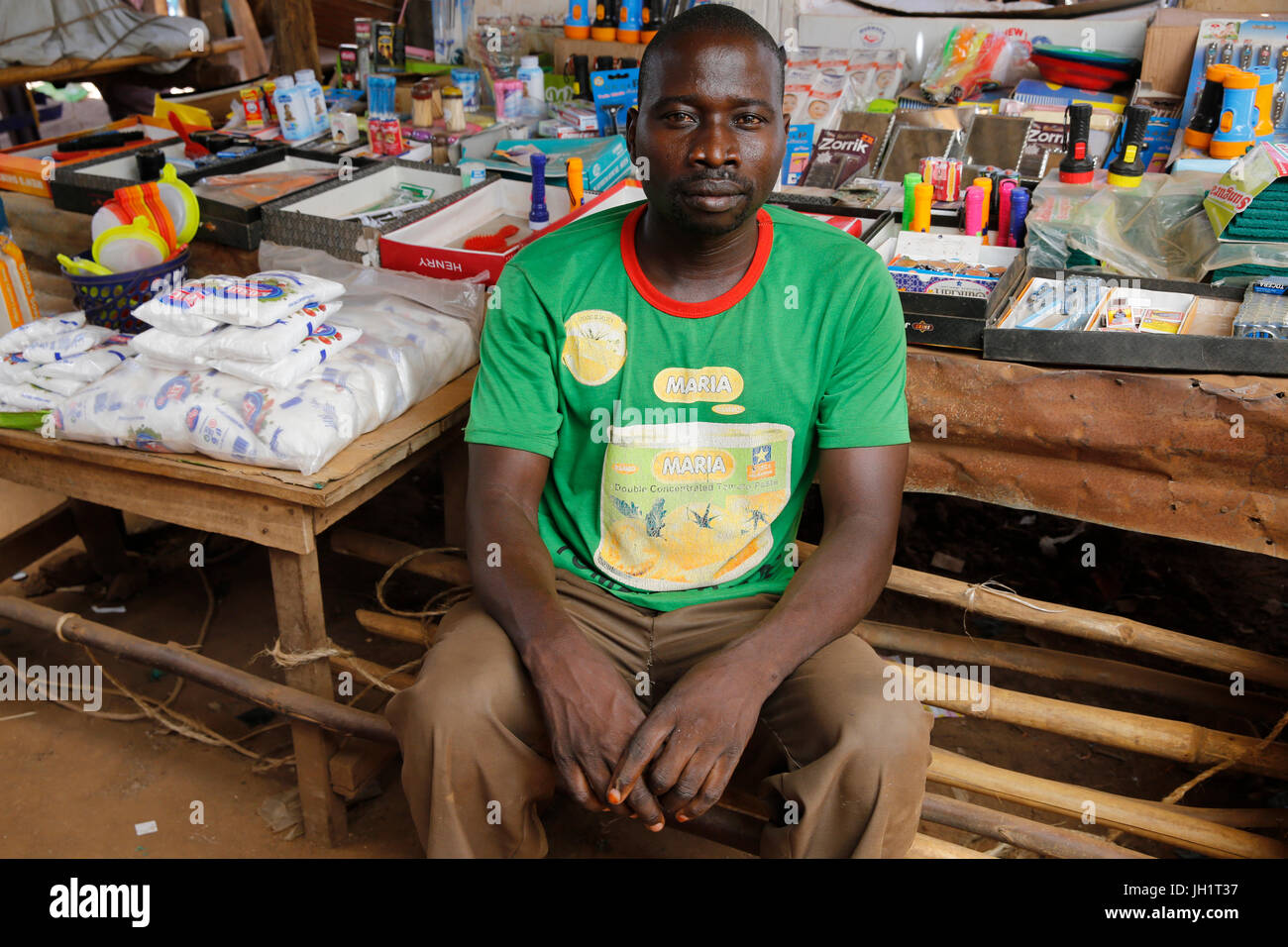Michael Nakuni runs a stall at Bweyale market. He received 4 loans from Uganda Microfinance Foundation. Uganda. - Stock Image