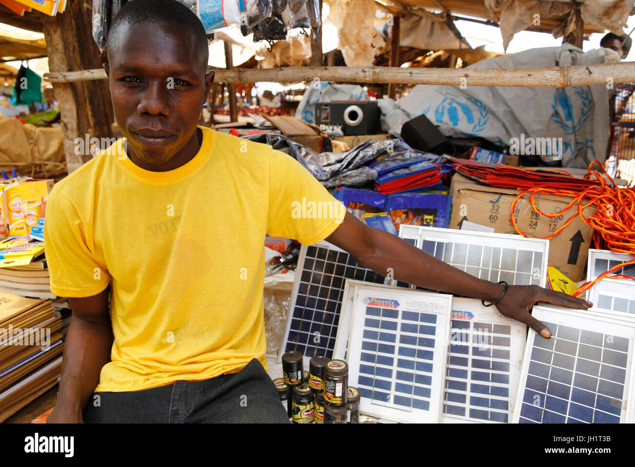 Robert Candia runs 2 stalls at Bweyale market. He received 3 loans from Uganda Microfinance Foundation.  Uganda. - Stock Image